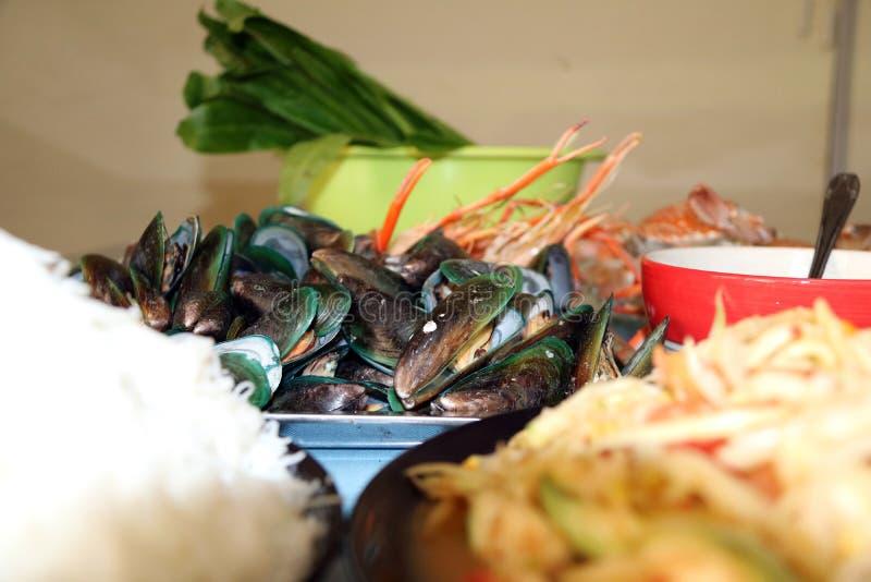 Hög av den bakade musslan på mitten av skaldjur, den bakgrund grillade lagade mat räka och gräsplangrönsaken i den gröna bunken arkivfoto