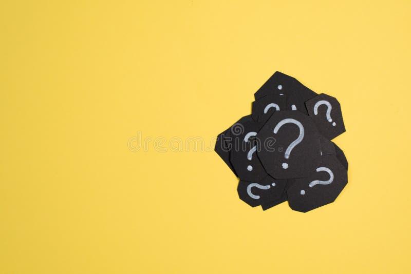 Hög av det svarta pappers- kortet med FRÅGEFLÄCKEN på ljus gul bakgrund royaltyfri fotografi