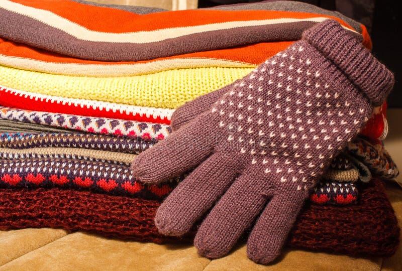 Hög av färgrik varm vinterjulkläder och en vinterglov royaltyfria foton