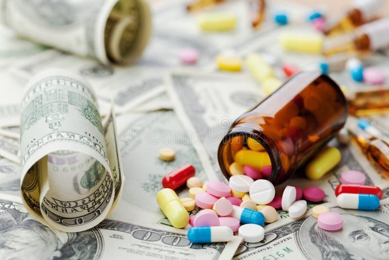 Hög av farmaceutiska drog- och medicinpreventivpillerar på dollarpengar, kostnad av sjukvård och medicinsk försäkring royaltyfri bild