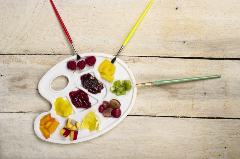 Hög av fruktskivor på den vita paletten för plast- konst, träbakgrund royaltyfri bild