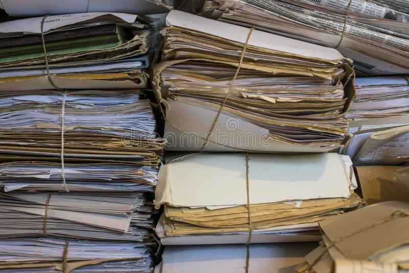Hög av gamla legitimationshandlingar och tidningar i arkivet arkivfoto
