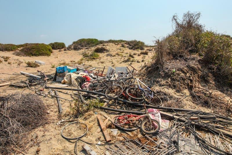 Hög av gamla rostiga kasserade cyklar som lägger på sand i stark sol Alla märken/borttagna logoer arkivbilder