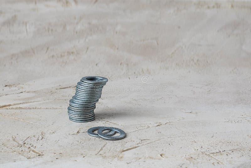 Hög av gråa hållare för packning för metalllåsflik för bultar och skruvar på grå cementbakgrund som är horisontal med kopieringsu royaltyfri fotografi
