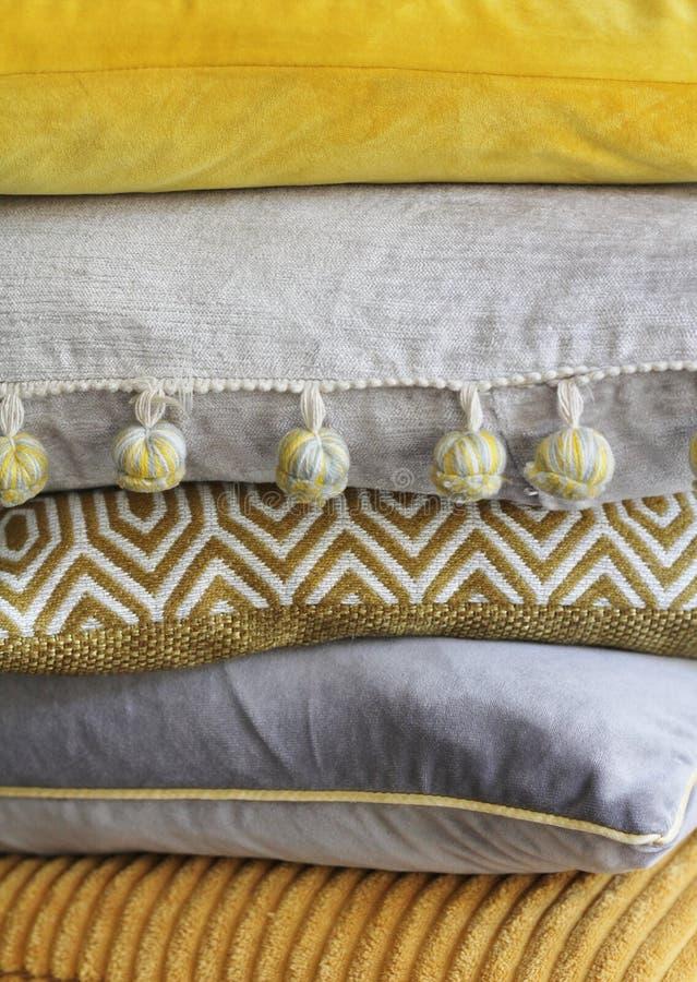 Hög av guling- och grå färgkuddar royaltyfri bild