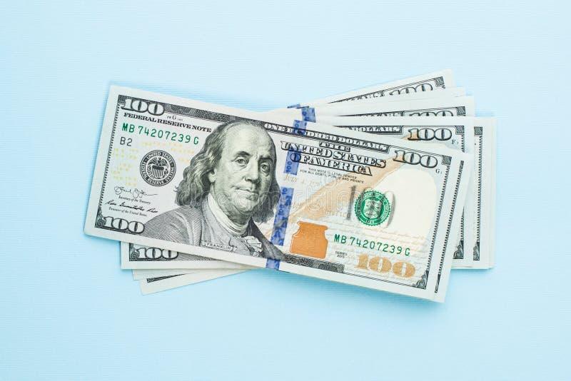 Hög av hundra dollar Moderna 100 oss dollarräkningar på blå bakgrund royaltyfri fotografi