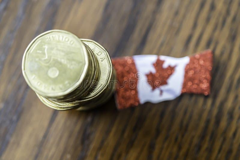 Hög av kanadensaren en dollar mynt med den kanadensiska flaggan fotografering för bildbyråer