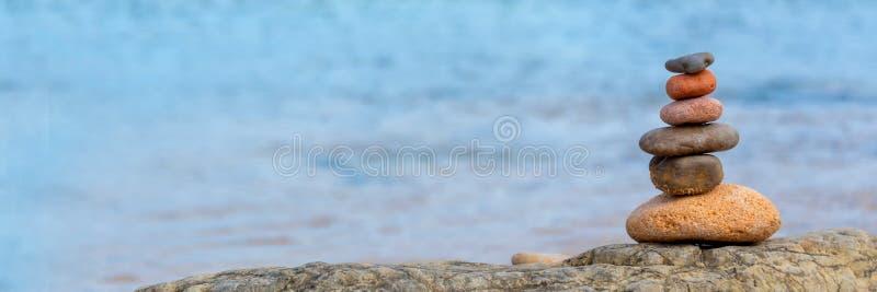 Hög av kiselstenar på bakgrund för blått vatten för strand en panorama- royaltyfri fotografi