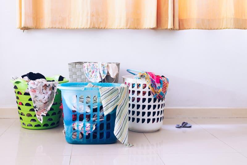 Hög av kläder i många tvättkorgar i hus arkivfoton