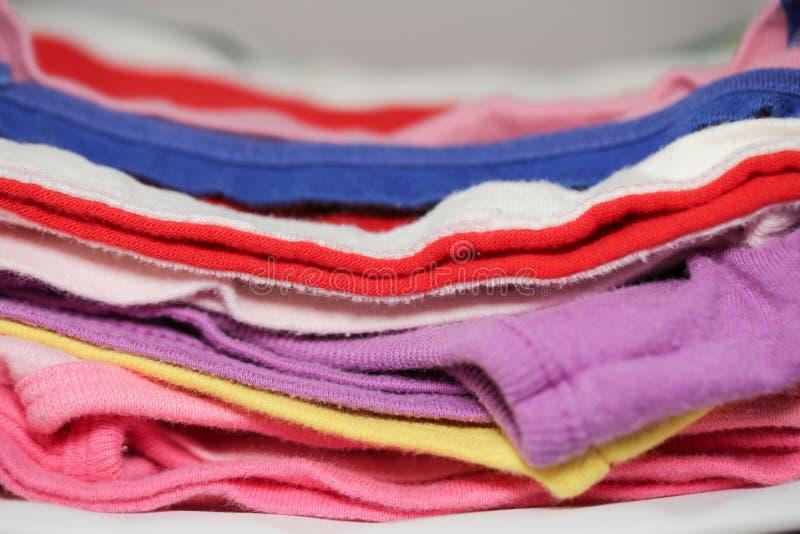 Hög av kläder på tabellcloseupen arkivbild