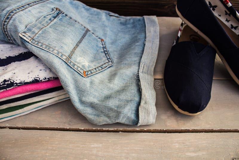 Hög av kläderen på skor för en tabell arkivbilder