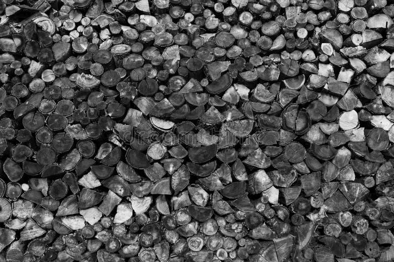 Hög av klippt trä som bakgrund, textur Vedträ svartvit bild arkivfoto