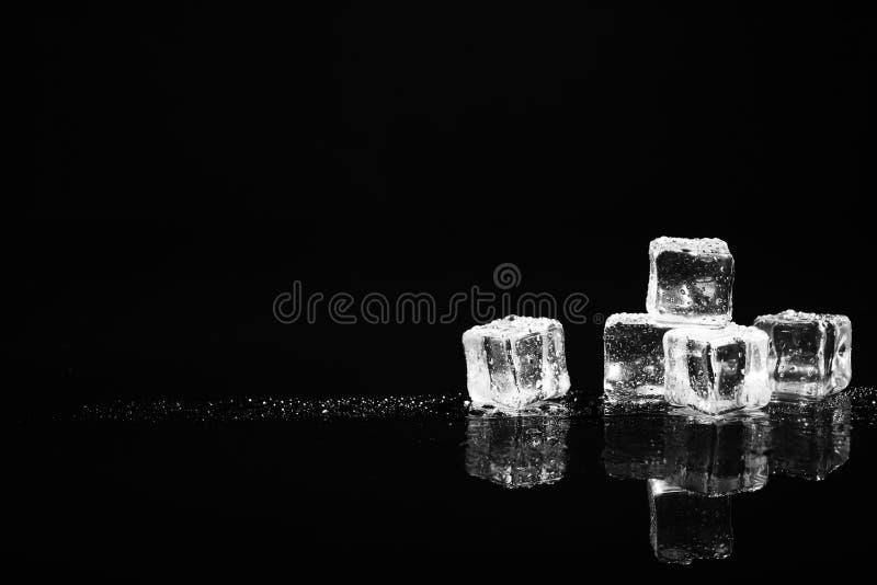 Hög av kristallklara iskuber på svart Utrymme för text arkivbilder
