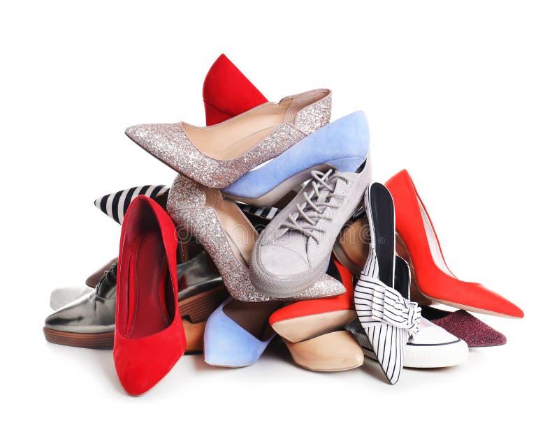 Hög av kvinnliga skor på vit arkivfoto