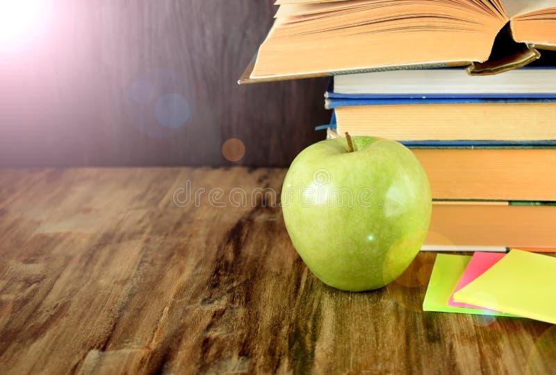 Hög av läroböcker och ett grönt äpple royaltyfri foto