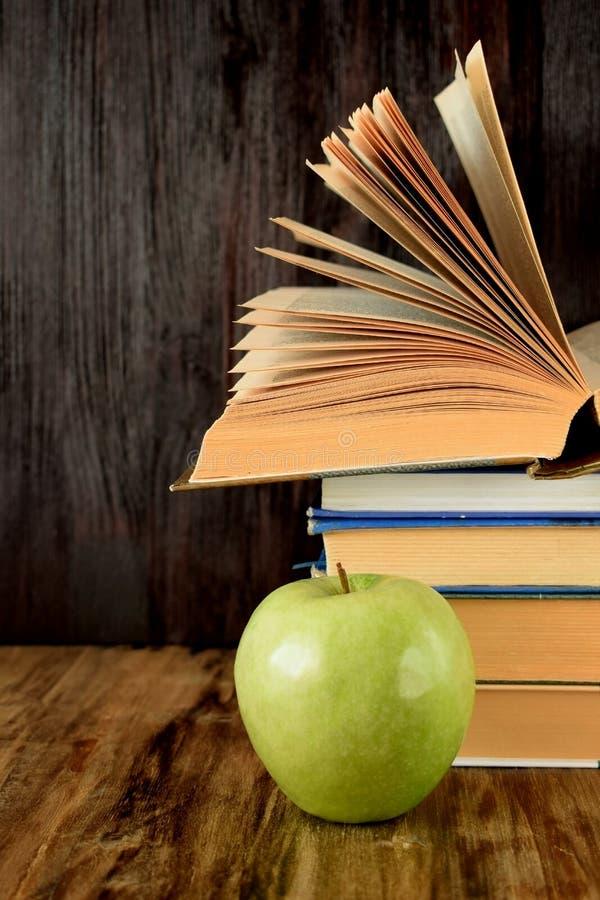 Hög av läroböcker och ett grönt äpple royaltyfri fotografi