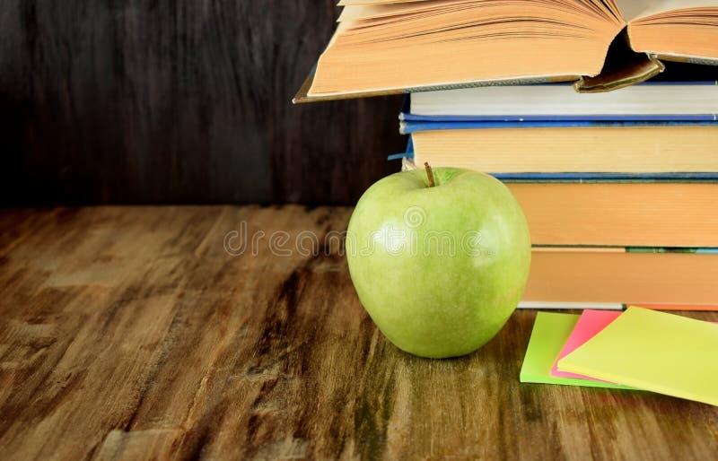 Hög av läroböcker och ett grönt äpple arkivfoto