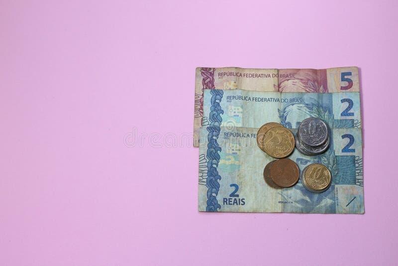 Hög av lågt värde för brasilianska pengar på rosa bakgrund med kopieringsutrymme för text royaltyfri foto