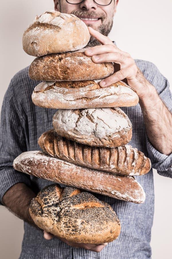 Hög av lantliga vresiga bröd i händer för bagareman` s arkivfoton