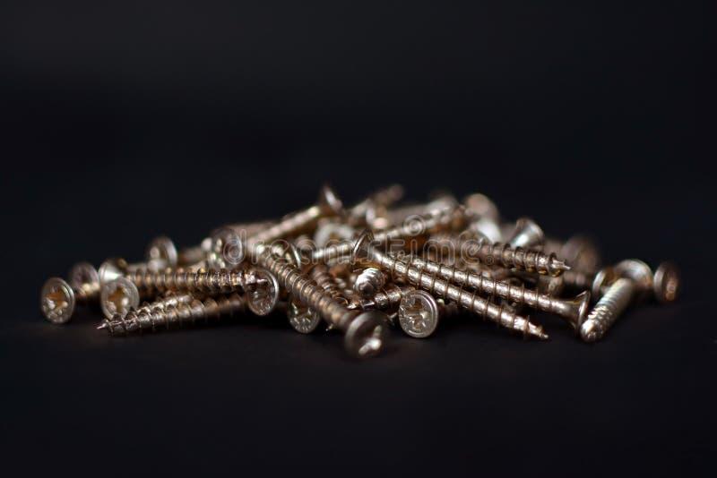 Hög av metalliska guld- skruvar på svart bakgrund arkivbild