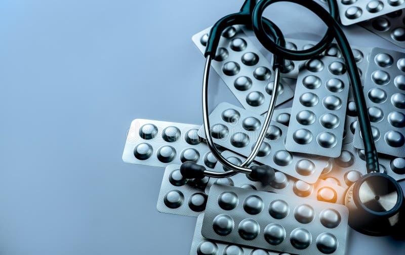 Hög av minnestavlapiller i packe och stetoskop för blåsa för silveraluminiumfolie på vit bakgrund Farmaceutisk bransch drog royaltyfria bilder