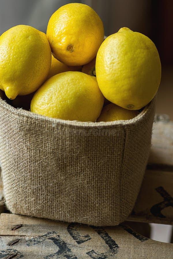 Hög av mogna organiska citroner i jutesäckanseende på träträdgårdasken Lantlig Kinfolkstil Atmosfärisk lynneslags tvåsittssoffaat royaltyfria foton