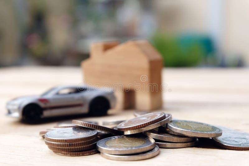 Hög av mynt med trähus- och bilmodellbakgrund En handinnehavkrus av pengar arkivbild