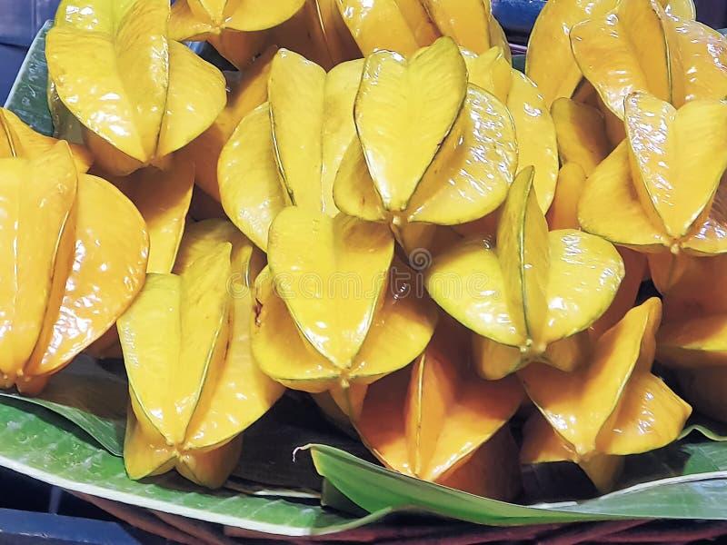 Hög av nya gula stjärnafrukter på bananbladet arkivbild