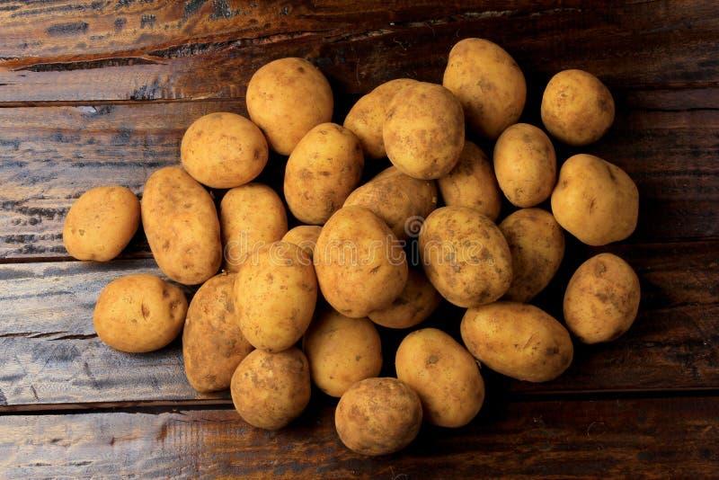 Hög av nya och rå potatisar som skördas från koloni och den förlade lantliga trätabellen arkivbilder