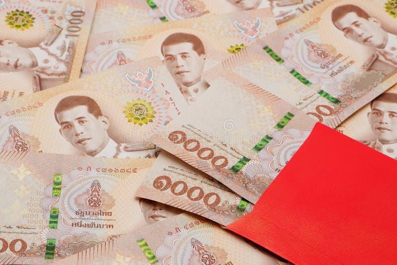 Hög av nya 1000 sedlar för thailändsk baht med det röda kuvertet royaltyfria foton