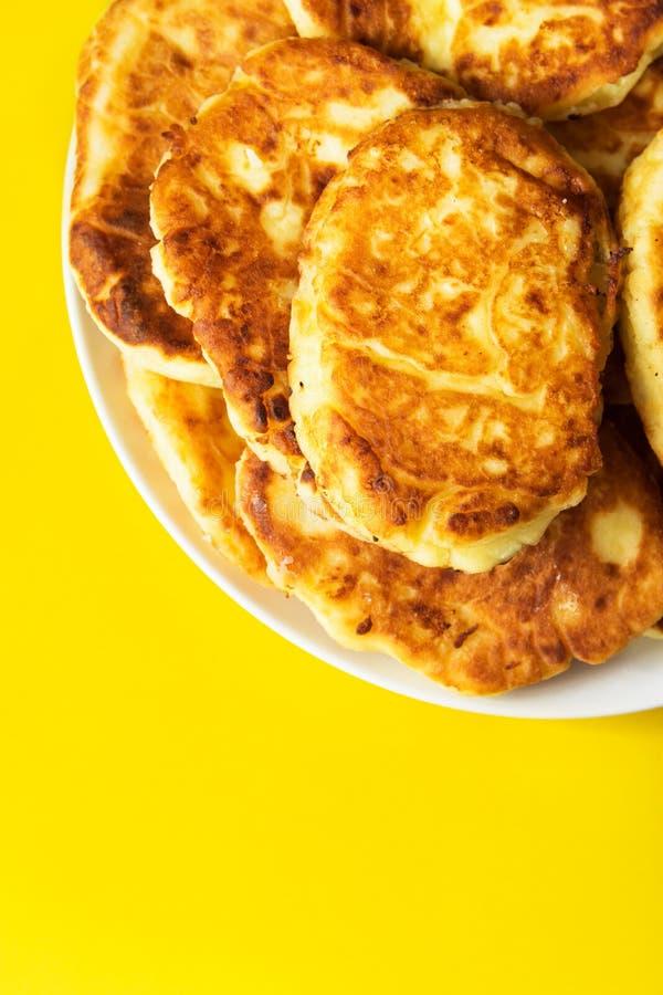 Hög av nytt stekte hemlagade fluffiga pannkakor från keso på plattan på ljus gul bakgrund Aptitretande guld- skorpa arkivbild