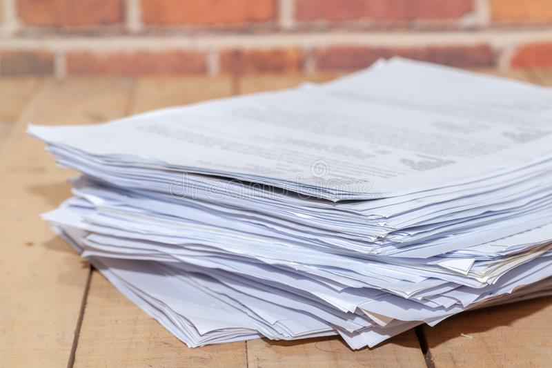 Hög av oavslutade dokument på kontorsskrivbordet arkivbilder