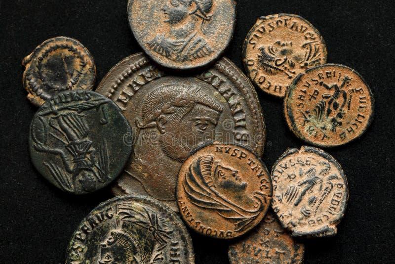 Hög av olika forntida mynt på svart bakgrund arkivbilder