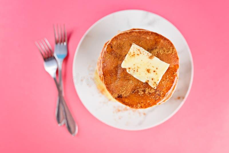 Hög hög av pannkakor med smör, honung, kanel överst royaltyfri bild