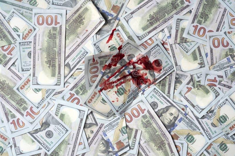 Hög av pengar med den blodiga fläcken, bästa sikt Smutsig brottslig vinst Dollar som markeras av mord Blodiga täckte valutapengar royaltyfri bild
