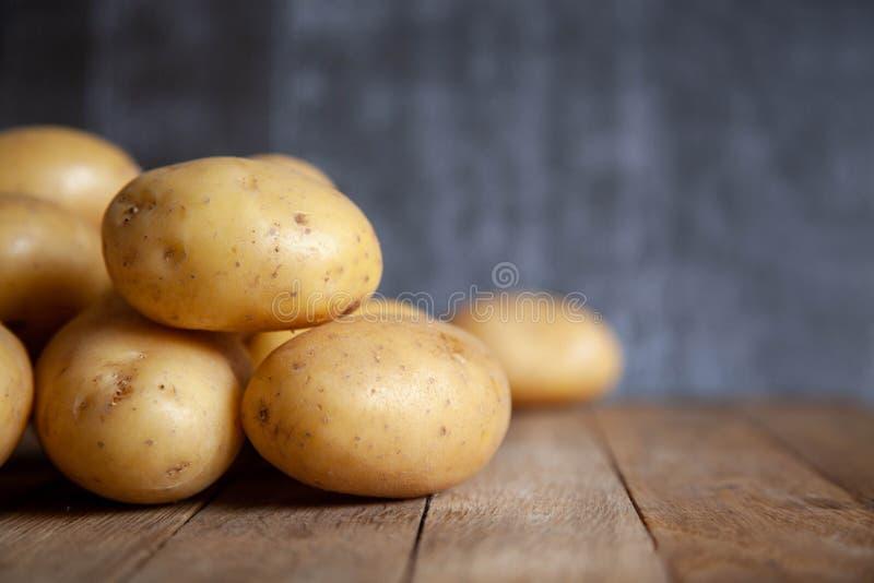 Hög av potatisar på den gamla trätabellen royaltyfri foto