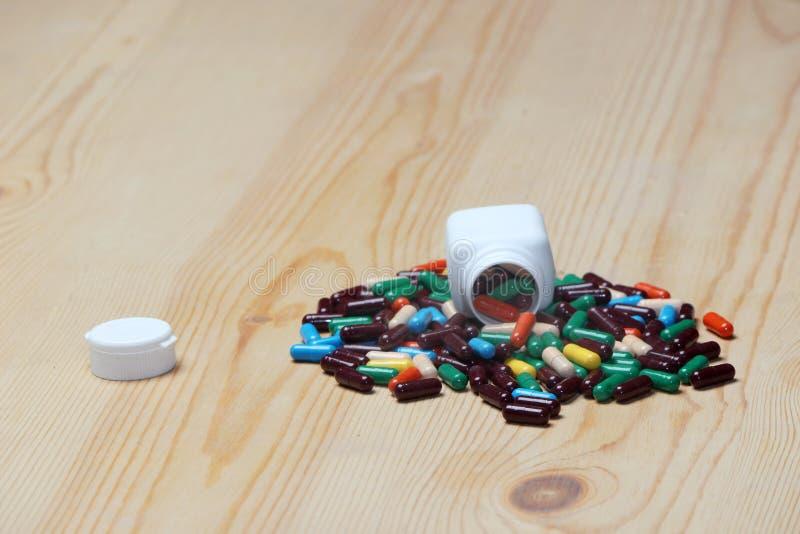 Hög av preventivpillerar med den vita flaskan och locket arkivfoton
