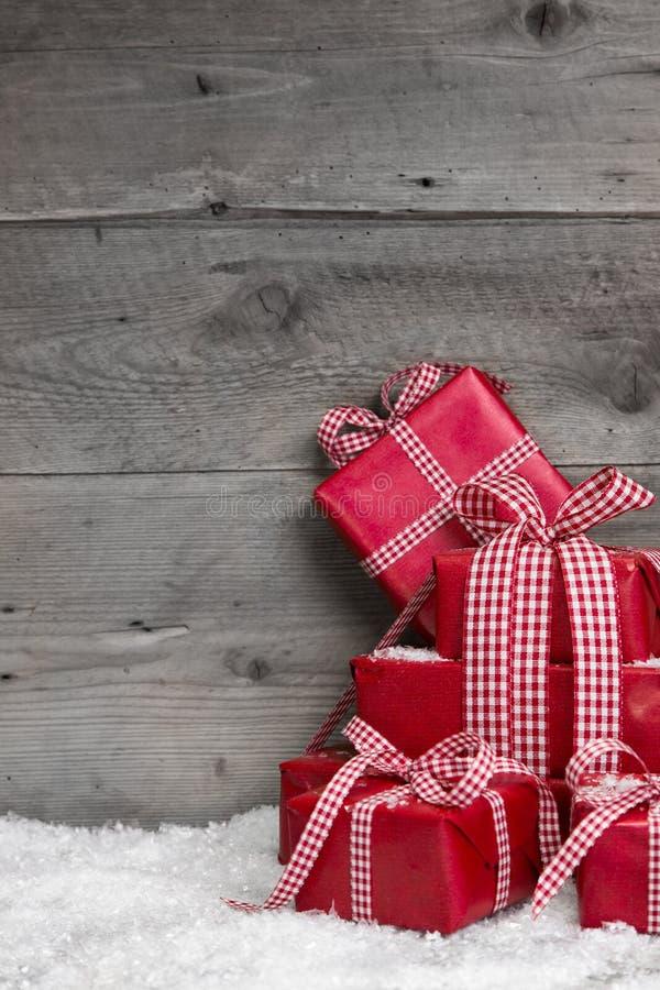 Hög av röda julgåvor, snö på grå träbakgrund. arkivbild