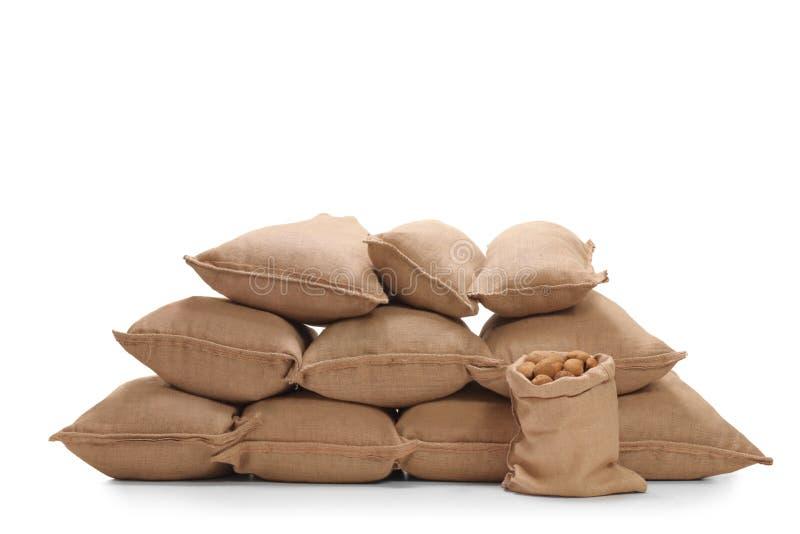 Hög av säckvävsäckar som fylls med potatisar arkivbilder
