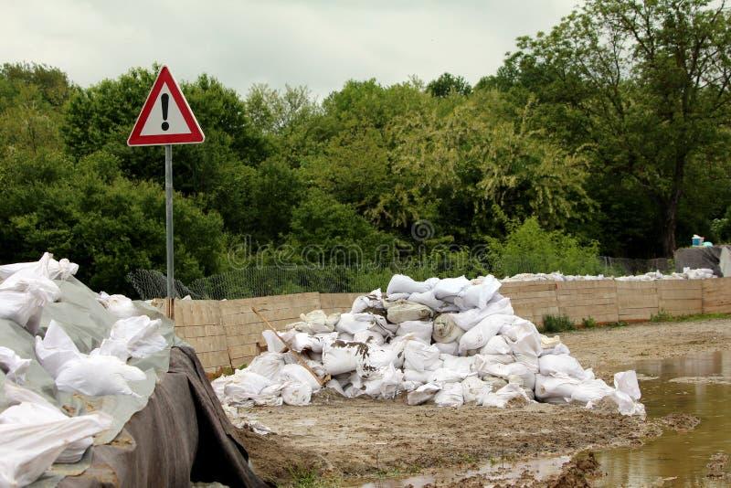 Hög av sandsäckar bredvid det varnande utropvägmärket och den tillfälliga väggen för flodskydd som göras av askbarriärer som täck arkivbilder