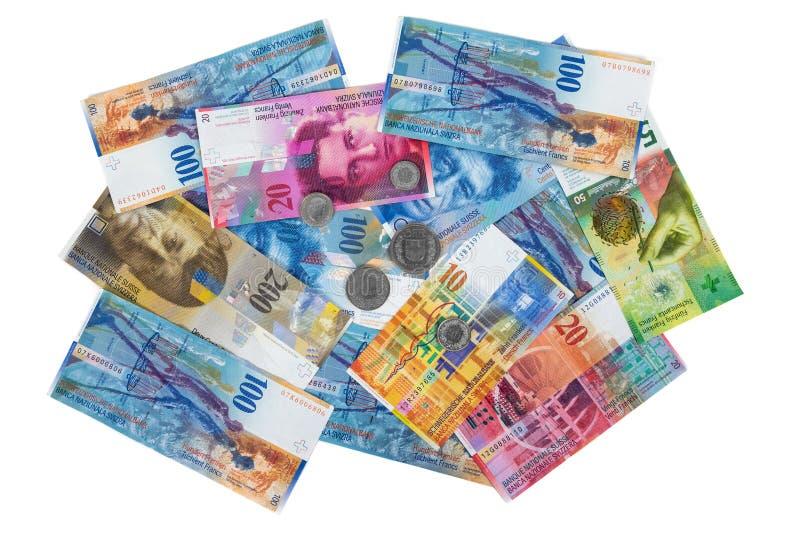 Hög av schweizisk francsedlar och mynt på vit bakgrund arkivfoton