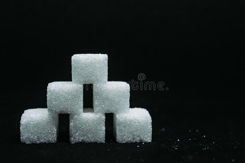 Hög av sikten för sockerkubcloseup på svart mörk isolerad bakgrund royaltyfri bild