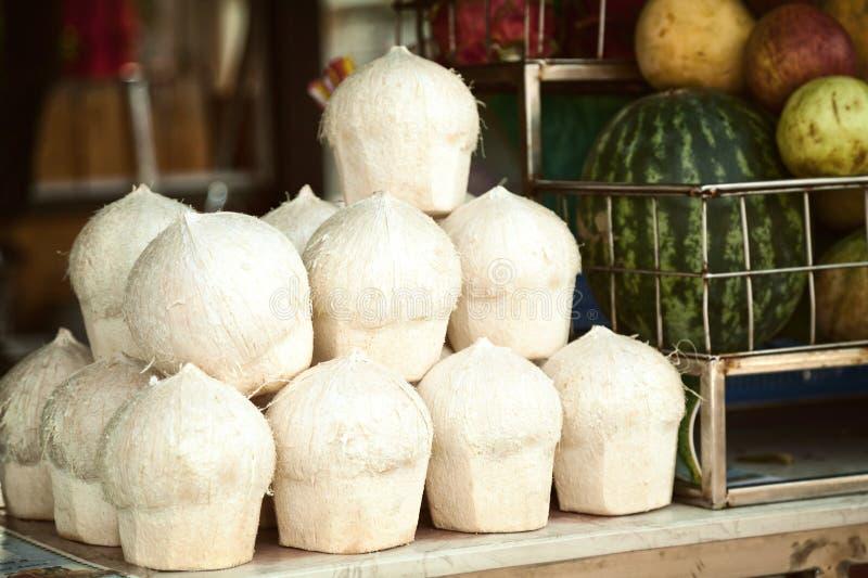 Hög av skalade cocos för att dricka på ett stånd royaltyfri fotografi