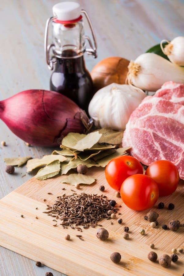 Hög av spiskumminkryddan bredvid den grisköttkött och grönsaken arkivbilder