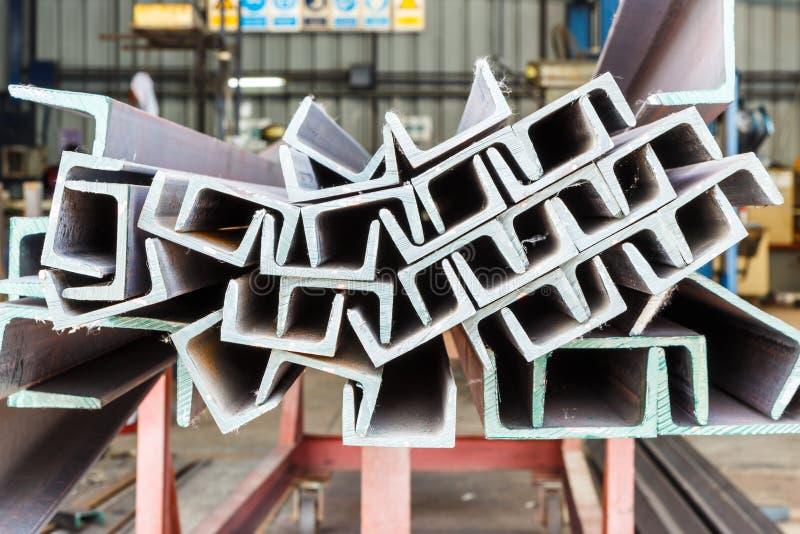 Hög av stål för U-formstråle i fabrikshylla royaltyfria bilder