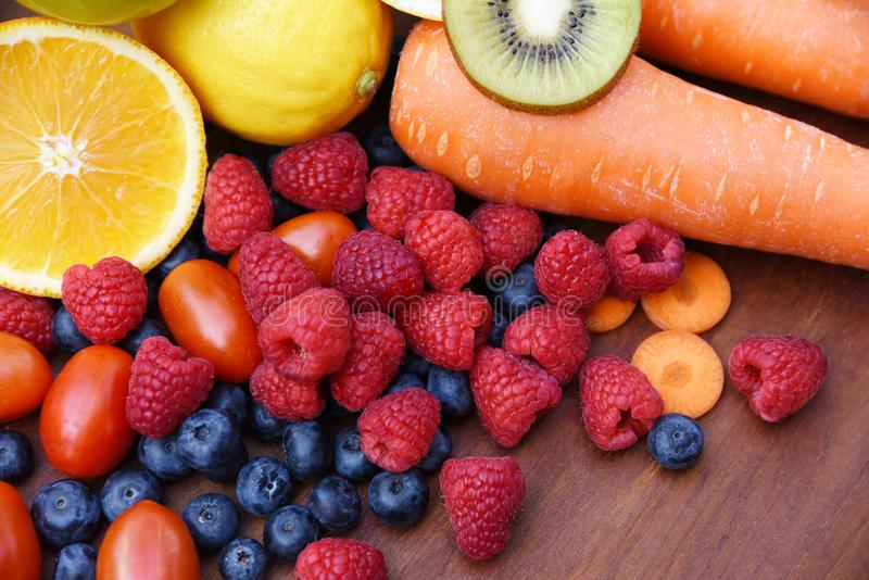 Hög av sund mat för ny färgrik grönsaksommar för tropiska frukter/många mogen frukt blandad på träbakgrund royaltyfria foton