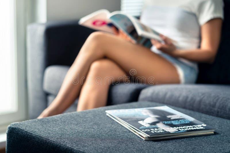 Hög av tidskrifter med damläsning i vardagsrum Mode- och skönhetspetsar eller kändisnyheterna Millennial koppla av för kvinna arkivfoton
