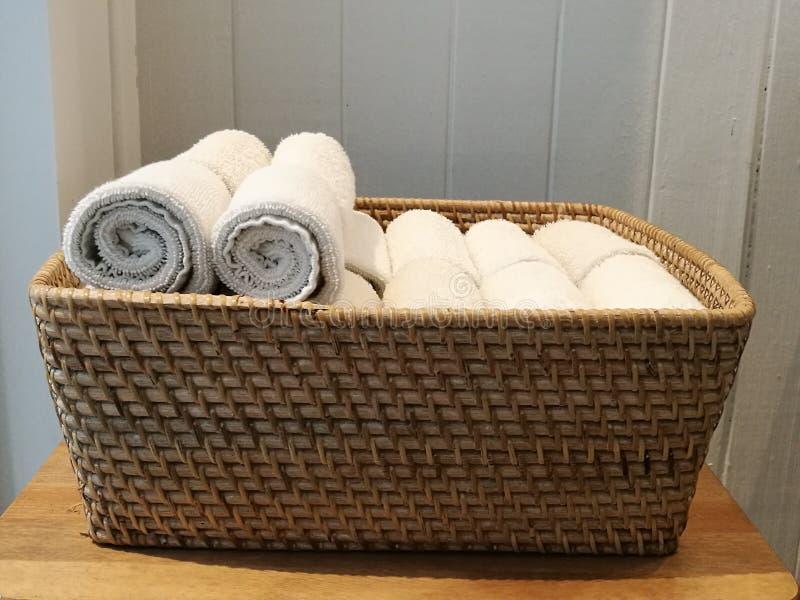 Hög av torkduken, handhandduk, tabellservett, näsduk på korgen i brunnsorten, badrum, toliet med den vita träväggbackgrouen för s fotografering för bildbyråer