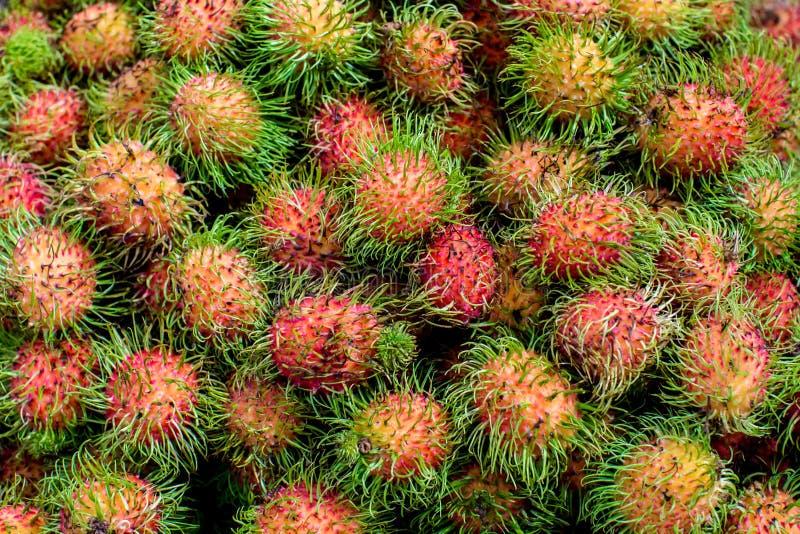 Hög av tropiska rambutanfrukter Den rosa och spetsiga rambutanen travas på en tabell på bönder marknadsför royaltyfria foton