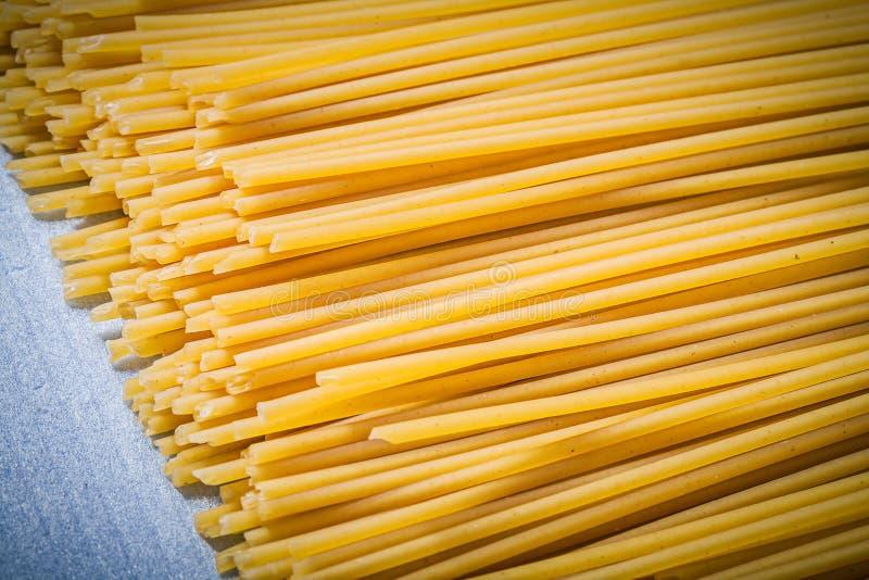 Hög av tunn spagetti på blå bakgrund direkt ovanför mat arkivfoton